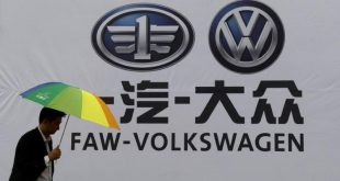 FILE PHOTO: A man holds an umbrella as he walks past a company logo of FAW-Volkswagen at an automobile exhibition in Fuyang